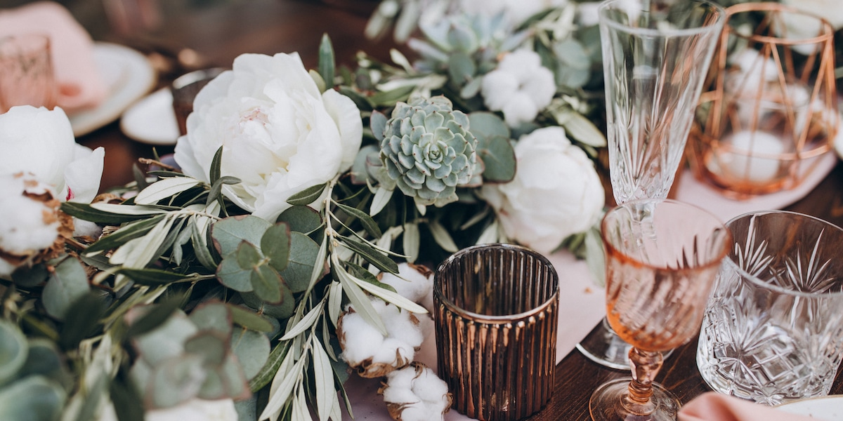 on wooden banquet table are glasses, plates, candles, table is d
